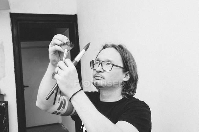 Ritratto di artista maschile che lavora nel suo laboratorio e guarda i pennelli — Foto stock
