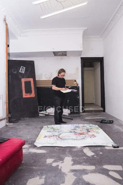 Creative male artist working in his workshop while holding sketchbook — Stock Photo
