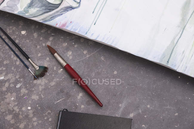 Brushes lying on floor near paper with painting — Stock Photo