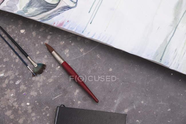 Кисти, лежащие на полу рядом с бумагой с живописью — стоковое фото