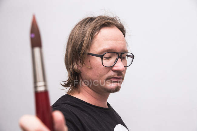 Portrait of male artist working in his workshop holding brush in hand — Stock Photo