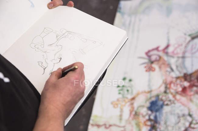 Creative male artist working in his workshop and painting in sketchbook — Stock Photo