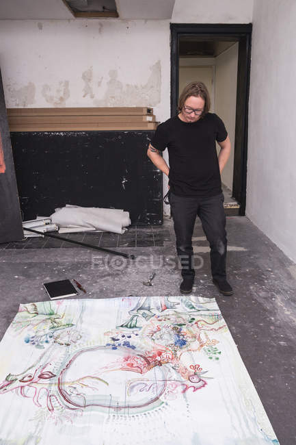 Creative male artist working in his workshop while looking down on paper — Stock Photo
