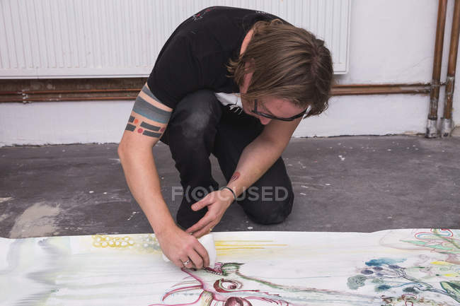 Creative male artist working in his workshop while painting on paper — Stock Photo