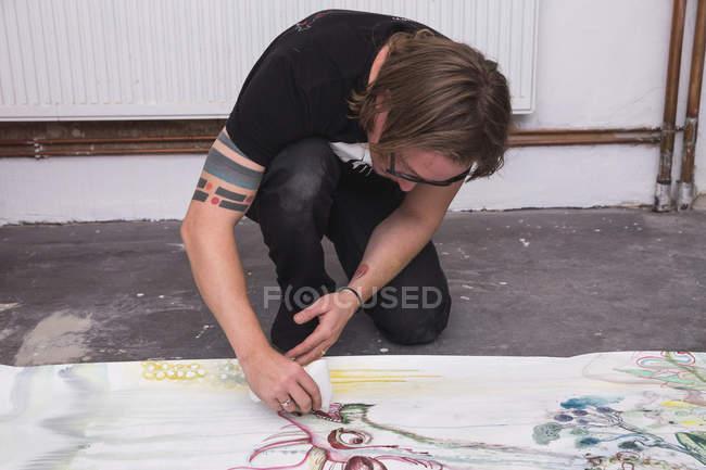 Творческий мужчина-художник работает в своей мастерской, рисуя на бумаге — стоковое фото