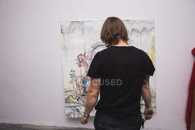 Задний вид творческого мужчины, работающего в своей мастерской . — стоковое фото