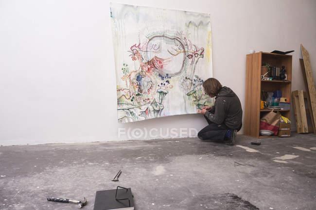Творческий мужчина, работающий в мастерской, стоя на коленях — стоковое фото