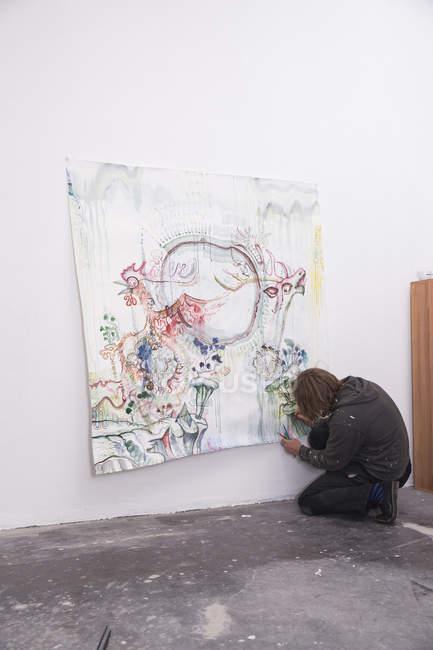 Artista creativo maschile che lavora nel suo laboratorio mentre si inginocchia — Foto stock