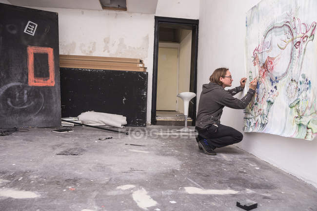Side view of Creative male artist working in his workshop. — Stock Photo