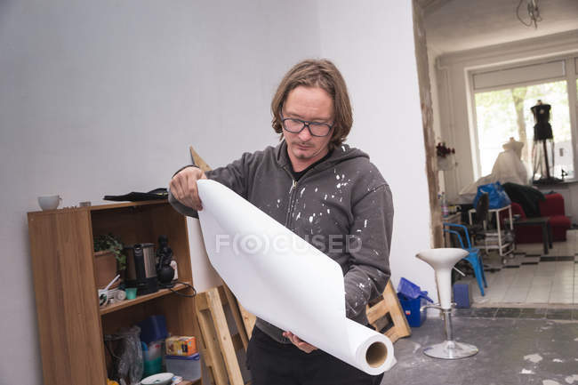 Creative male artist working in his workshop and holding paper in hands — Stock Photo