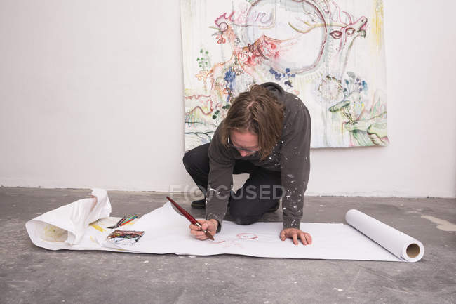Creative male artist working on floor in his workshop — Stock Photo