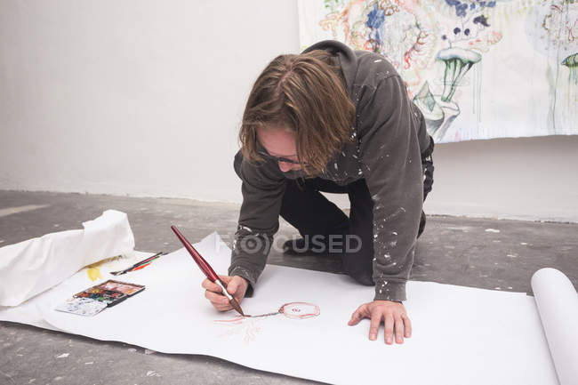 Front view of kneeling Creative male artist working in his workshop. — Stock Photo
