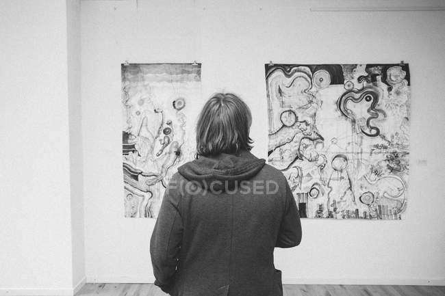 Rear view of Creative male artist watching his art piece in an art gallery. — Stock Photo