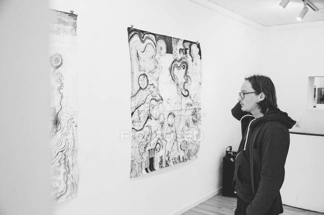 Black and white shot of Creative male artist watching his art piece in an art gallery. — Stock Photo
