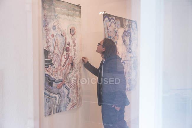 Männliche Künstler sein Kunstwerk an der Wand in einer Kunstgalerie ansehen — Stockfoto