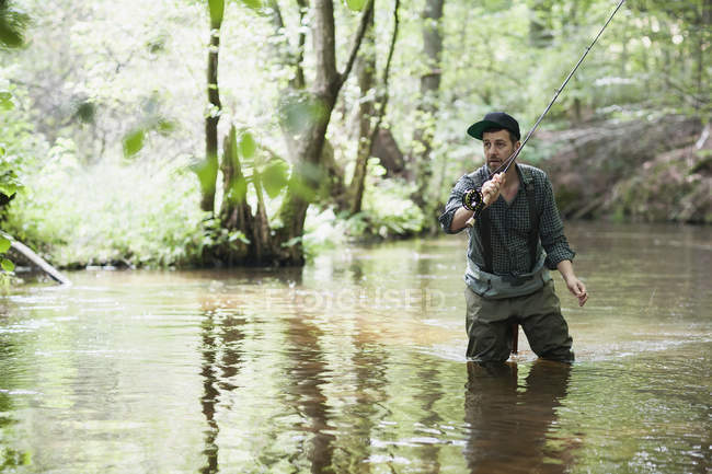 A patient man in waders is fly fishing on river in forest area. — Stock Photo