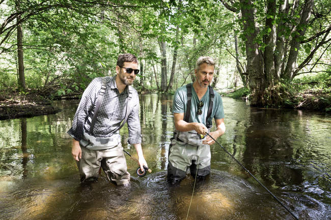 Two men in waders are fly fishing on river in forest area. — Stock Photo