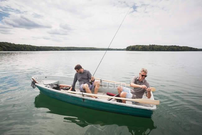 Two caucasian men are preparing their equipment for fly fishing from a boat on lake. — Stock Photo
