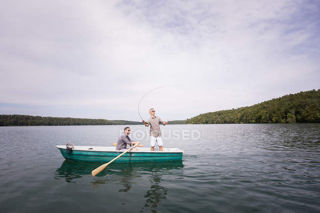 A man is rowing a rowboat while his friend is fly fishing from a boat on lake. — Stock Photo