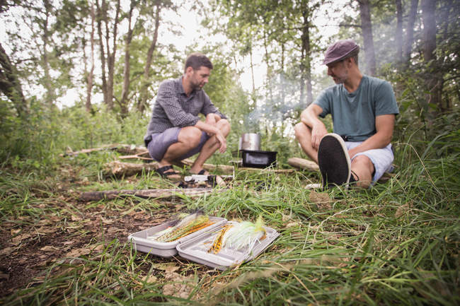 Fly fishing tackle in grass while two fly fishers do a barbecue in wild nature. — Stock Photo