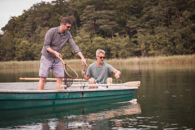 Homens caucasianos são pesca com mosca em barco na água do lago — Fotografia de Stock