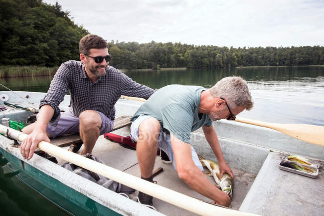 Two fly fishers have catched a pike from a boat on a lake. — Stock Photo