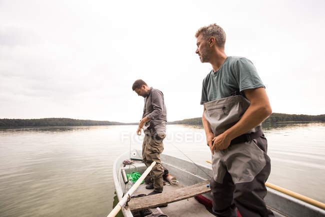 Two men are putting on waders before fly fishing from a lake. — Stock Photo