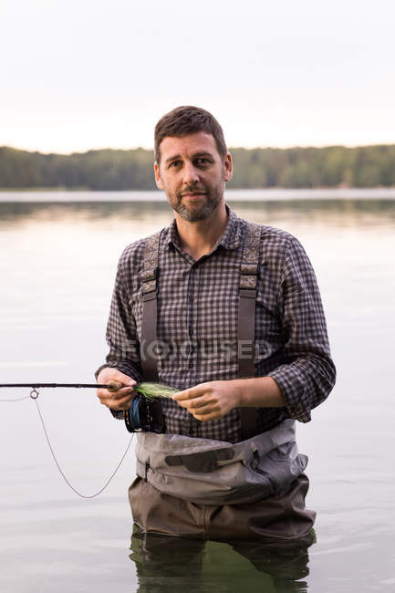 Front view of  man in waders is fly fishing in a lake. — Stock Photo