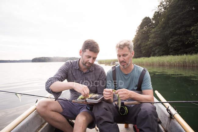 Due uomini stanno prendendo una pesca a Mosca da un'attrezzatura di pesca mosca in barca sul fiume. — Foto stock
