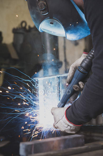 A blacksmith wears safety gear and is welding a metal construction in a metalsmith's workshop. — Stock Photo