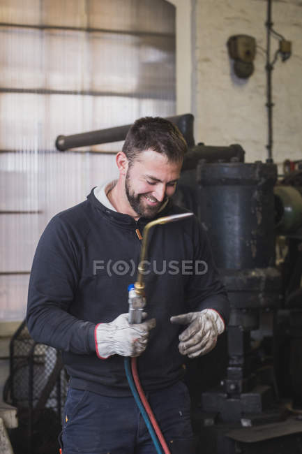 A smiling blacksmith is using a cutting torch in his workshop. — Stock Photo