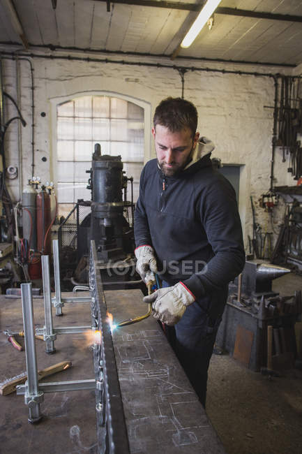 A blacksmith is using a cutting torch in his workshop. — Stock Photo
