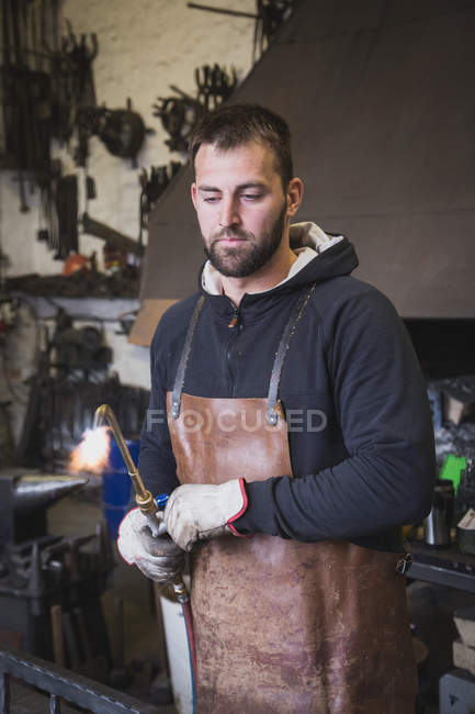 A blacksmith in a leather apron is using a cutting torch in his workshop. — Stock Photo
