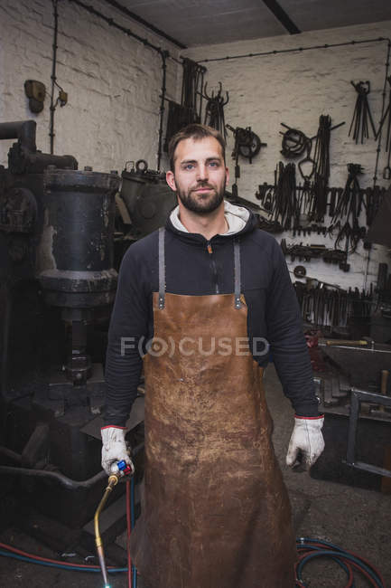 A blacksmith in a leather apron and with a cutting torch is portrayed in his workshop. — Stock Photo