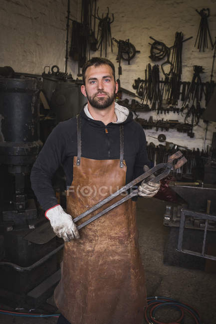 A blacksmith in a leather apron carries a tong and is portrayed in his workshop. — Stock Photo