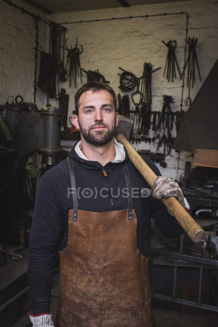 A blacksmith in a leather apron and with a sledgehammer is portrayed in his workshop. — Stock Photo