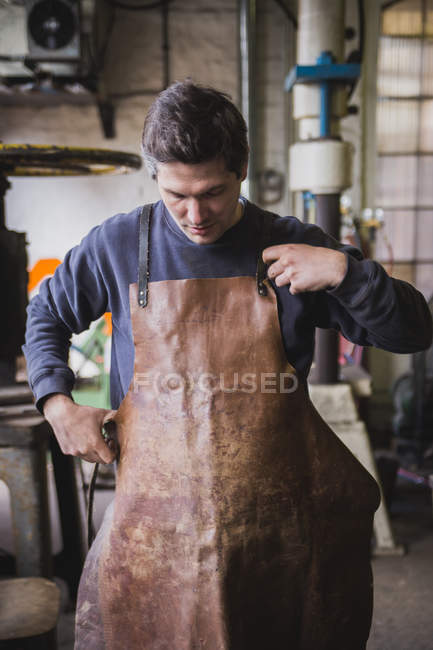 A blacksmith puts on a leather apron in a workshop. — Stock Photo