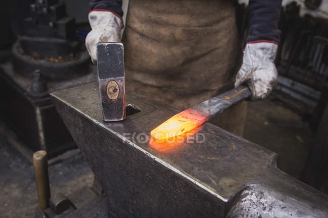 A blacksmith hammers a piece of hot metal on an anvil in a workshop. — Stock Photo