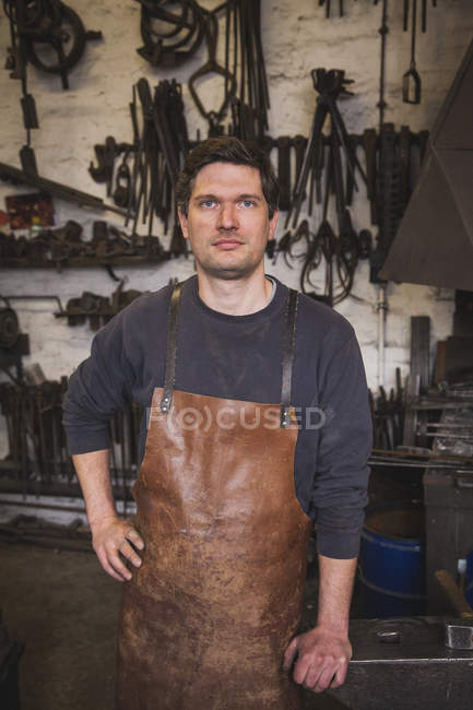 A blacksmith wears a leather apron and is portrayed in his workshop. — Stock Photo