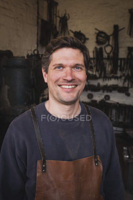 A smiling blacksmith wears a leather apron and is portrayed in his workshop. — Stock Photo