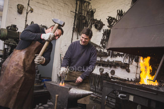 Two blacksmiths hammer a piece of metal on an anvil in a workshop. — Stock Photo