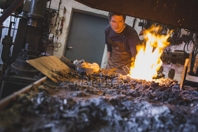 A blacksmith is heating up an iron bar in a workshop. — Stock Photo