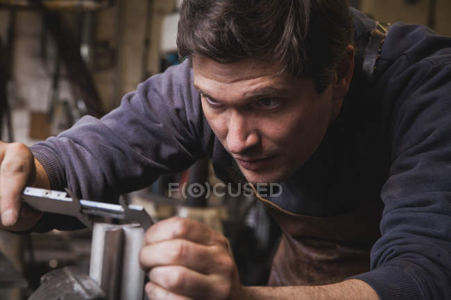 A blacksmith is taking measures on a piece of metal in a workshop. — Stock Photo