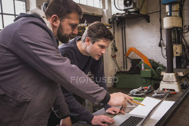 Two blacksmiths are taking measures, do calculations and schedule a days work on the computer in a blacksmith's workshop. — Stock Photo