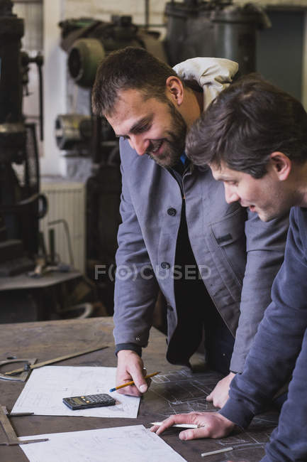 Two blacksmiths are taking measures, do calculations and schedule a days work in a blacksmith's workshop. — Stock Photo