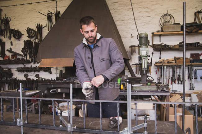 Un herrero se pone sus guantes de seguridad y su equipo de trabajo antes de trabajar en una pieza de metal en un taller . - foto de stock