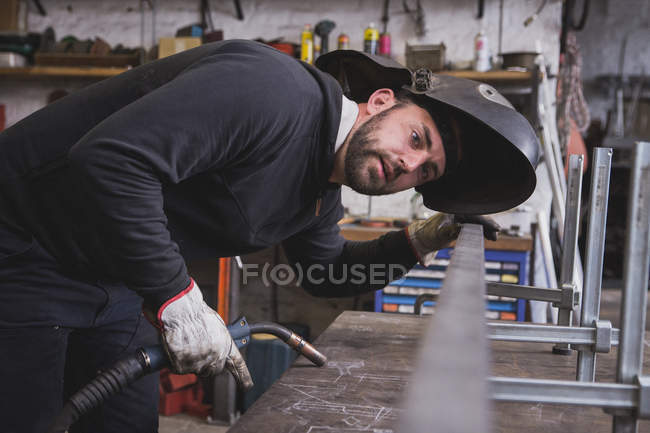 A blacksmith wears safety gear is taking measures before welding a metal construction in a metalsmith's workshop. — Stock Photo