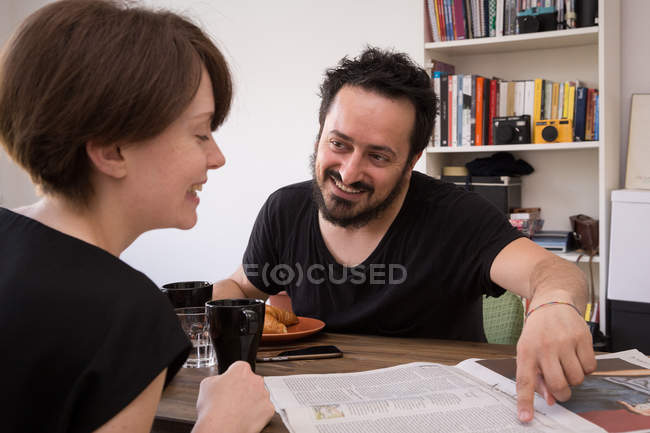 A young couple read newspaper at the breakfast table during a weekend at home. — Stock Photo