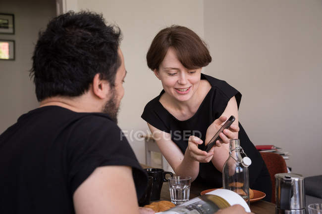 Young woman is checking her smart phone during breakfast and sharing news with her boyfriend. — Stock Photo