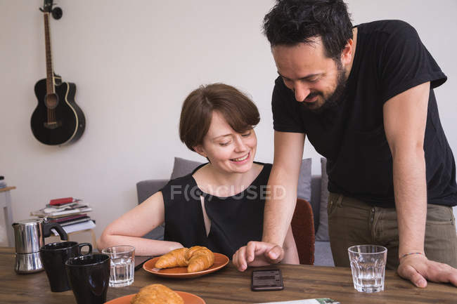 A young couple is cheacking social media on the smart phone at the breakfast table. — Stock Photo